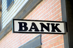 Old Wooden Bank Sign. Close up of an old wooden bank sign with brick facade in background stock images