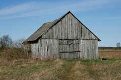 An old wooden barn. Old wooden barn at edge of field stock photo