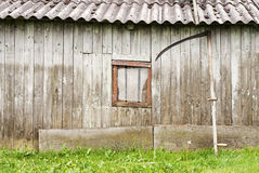 Old wooden barn. With broken window and scythe leaning against a wall Stock Photography