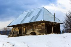 Old wooden barn in the countryside, modern roof in winter Royalty Free Stock Photo