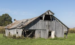 A old wooden barn decaying. An old wooden barn decaying in a rural area on a rural road stock photo