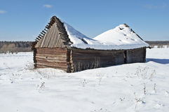Old wooden barn under snow. Old wooden barn with a snow-covered sagging roof, winter sunny day Stock Photo
