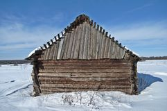Old wooden barn on a snowy field Stock Image