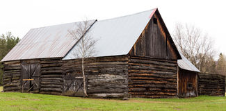 An old wooden barn in spring. Old wooden barn falling apart and weathered over time Royalty Free Stock Photos
