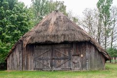 Old wooden barn with a thatched roof royalty free stock image