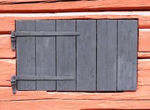 Old wooden barn window background. Wooden shutter painted grey on a very old pink painted barn in Sweden Royalty Free Stock Photo