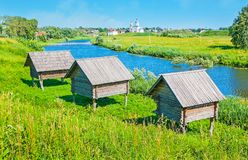 Old barns in Suzdal. The old wooden barns on stilts, located on the green bank of Kamenka river, Suzdal, Russia Stock Images