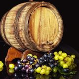 Old wooden barrel and grapes. Royalty Free Stock Images