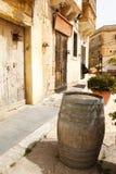 Old wooden barrel on narrow street Mdina, Malta. Old wooden barrel on narrow street in Malta. Maltese architecture in Mdina, Malta 2013 Stock Photography