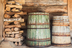 Old wooden barrels and firewood Stock Images