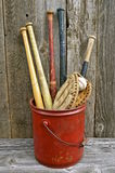 Old wooden baseball bats. Old wood baseball bats, leather glove, and ball are stored in a vintage red five gallon pail stock photos