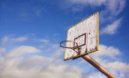 Old wooden basketball board. In blue cloudy sky background stock photo