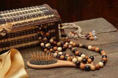 Old wooden beads, wooden casket and hairbrush on table Stock Image