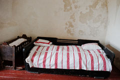 Old wooden bed with child cradle background ragged wall.  Royalty Free Stock Photos