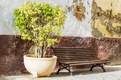 An old  wooden bench against a weathered wall in Spain. Stock Photography