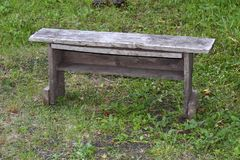 Old wooden bench on a background of green grass Royalty Free Stock Photo