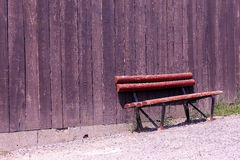 Old wooden bench. By an old barn wall Stock Photo