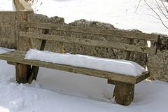 Old wooden bench covered with snow in Northern Italy Stock Photo