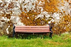 Old wooden bench on green grass near the moss covered stone stock images