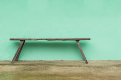 Old wooden bench and green wall Stock Image