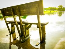 Old wooden bench Installed on the cement floor after rain, flooded the ground. Royalty Free Stock Photography
