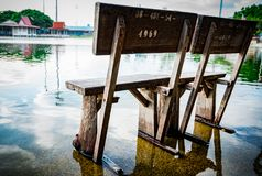 Old wooden bench Installed on the cement floor in the temple after rain, flooded the ground. Royalty Free Stock Image