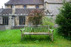 Old wooden bench outside stone church. An old wooden bench covered in lichen stands in a grassy yard outside a stone church in England Stock Photography
