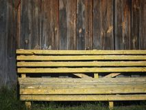 Old Painted Bench. Old wooden bench painted in yellow against the grunge barn wall Stock Photography