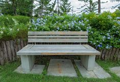 Garden bench surrounded by flower. Old Wooden bench in the park royalty free stock photo