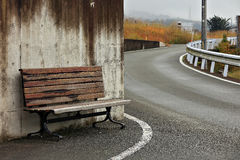 Old wooden bench on sidewalk on road Royalty Free Stock Photography