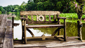 Old wooden bench in a tropical water garden Royalty Free Stock Photography