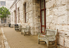 Old Wooden Benches Along Stone Block Wall Royalty Free Stock Images