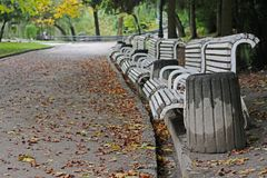 Old wooden benches and concrete bins in an autumn city park. Old white wooden benches and concrete bins in an autumn city park stock image