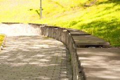 Old wooden benches on a stone elevation in the park stock image