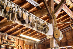 Old wooden Block and tackle pulleys in a boat builders shop. Old wood block and tackle and pulleys hanging in a chesapeake bay boat builders workshop Royalty Free Stock Images