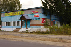 Old wooden blue barrack made of wooden planks with porch and signs in Russian - CAFETERIA, CANTEEN, PRODUCTS SHOP beside the road stock photo