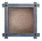 Old wooden blue frame against on a brown fabric background with copy space in the centre Stock Photo