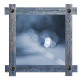 Old wooden blue frame with nails in shape of sun against a white background with blurred road, copy space in the center Royalty Free Stock Images