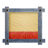 Old wooden blue frame with nails in shape of sun against a white background with sandy copy space in the center. Stock Photo