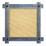 Old wooden blue frame with nails in shape of sun against a white background with sandy copy space in the center Stock Image