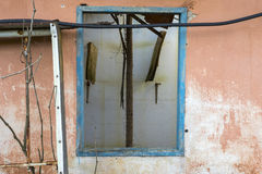 Old wooden blue window frame on an orange wall of an abandoned house Stock Photos
