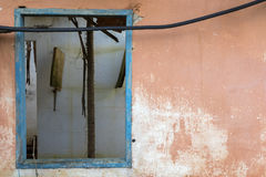 Old wooden blue window frame on an orange wall of an abandoned house Royalty Free Stock Image