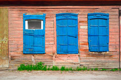 Old wooden blue window of slum house in Astrakhan, Russia Stock Photos