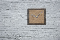 Old wooden board with clock hands on white bricks wall Royalty Free Stock Photos