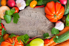 Old wooden board for text, spices and fresh vegetables, top view Royalty Free Stock Photo