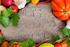 old wooden board for text, spices and fresh vegetables, top view Royalty Free Stock Photos