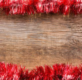 Old wooden boards framed by red tinsel Stock Image