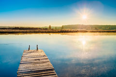 Old wooden boards pier on Calm Water Of Lake Royalty Free Stock Photography
