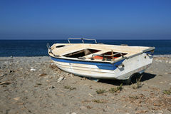 Old Wooden Boat. Low angle view at an old boat lying on the beach with some junk in the sand over cloudless sky Stock Photos