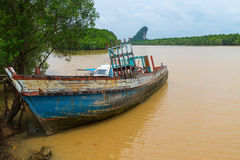 Old Wooden Boat, Abandoned and Deteriorating on a Muddy River Royalty Free Stock Photography